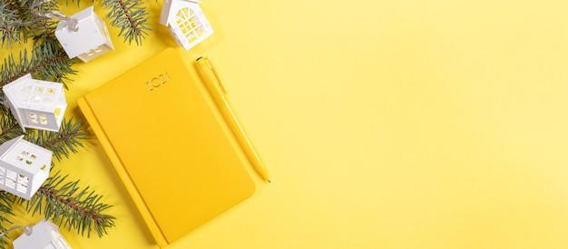 Желтый блокнот или планировщик на 2021 год с еловыми ветками и желтым фоном. вид сверху.
