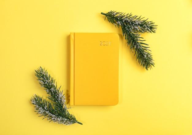 Желтый блокнот или ежедневник на 2021 год с еловыми ветками. вид сверху.