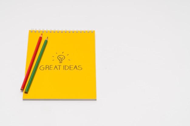分離された、白い背景の上の色鉛筆と黄色のメモ帳。学校に戻る。素晴らしいアイデア