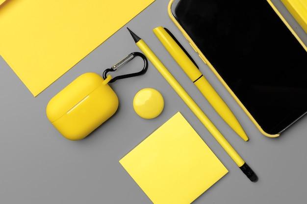 스마트 폰 및 펜 회색 배경에 노란색 메모장을 닫습니다.
