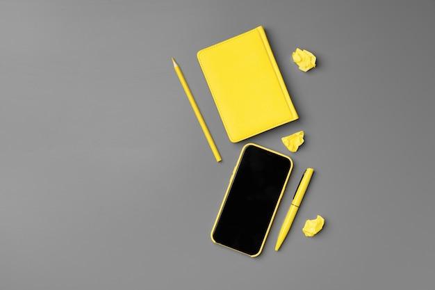 스마트 폰 및 펜 회색에 노란색 메모장을 닫습니다.