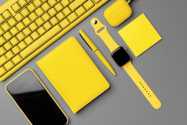 스마트 폰, smartwatch 및 회색 배경에 이어폰 노란색 메모장