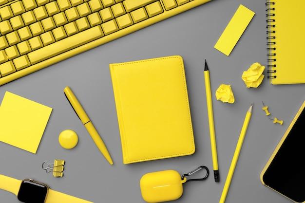 회색 표면에 스마트 폰, 스마트 워치 및 이어폰이있는 노란색 메모장