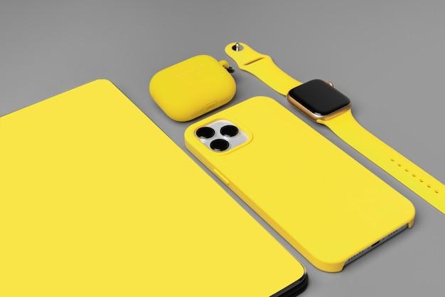스마트 폰, 스마트 워치 및 회색 이어폰이있는 노란색 메모장