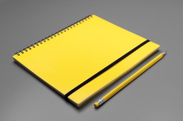 회색에 노란색 연필로 노란색 메모장을 닫습니다.