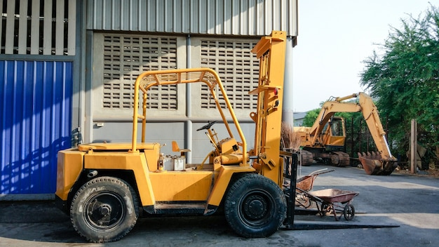 Yellow old excavator loader at factory. rust and grunge fork lift.