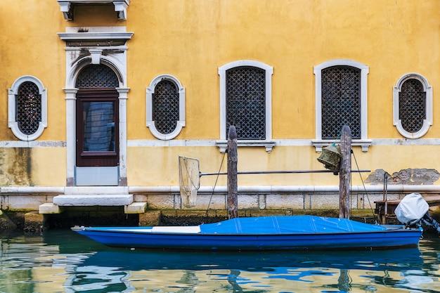 Желтый старый фасад и моторная лодка в канале города кьоджа в венето, италия