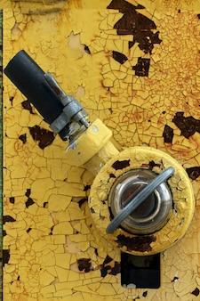 ガソリンスタンドの黄色い古い断片。燃料供給ホースまたはハンドルスイッチスイッチ、古いぼろぼろのヴィンテージ