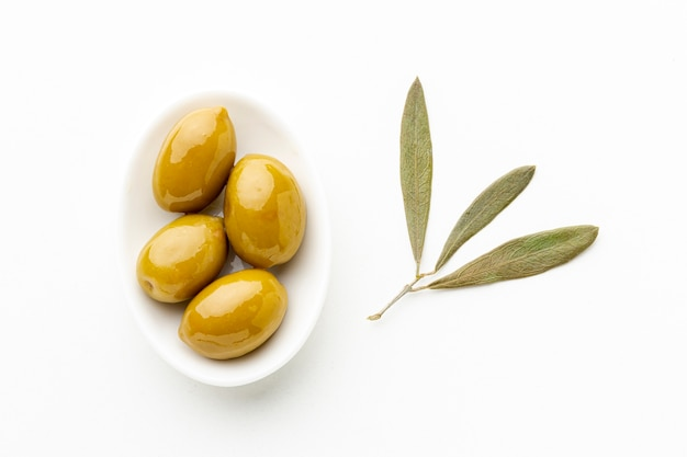 Yellow olives on plate with leaves