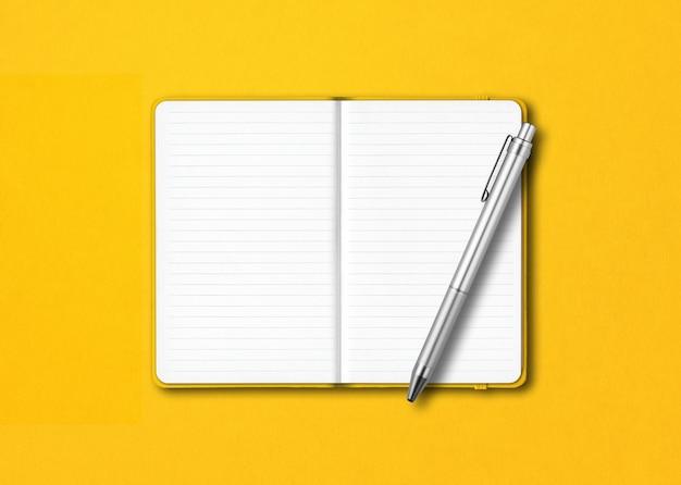 カラフルなテーブルに分離されたペンと黄色のオープンラインのノートブック