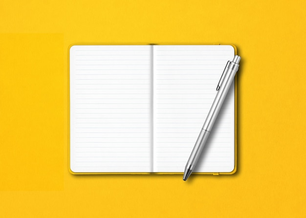 Yellow open lined notebook with a pen isolated on colorful table