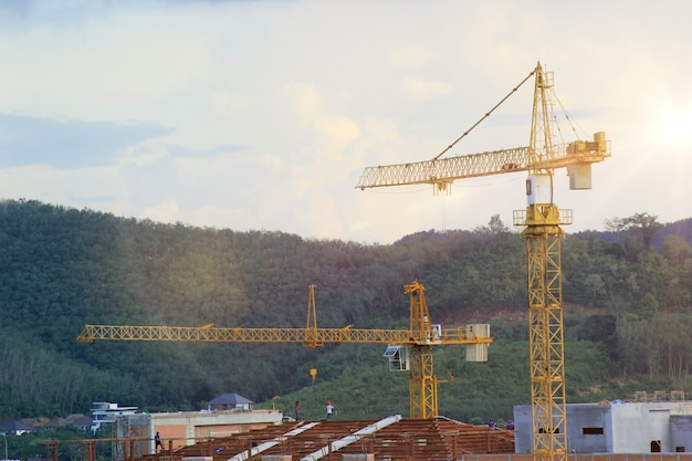 Yellow and orange construction tower cranes of mountains and sky.