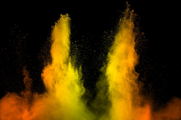 Yellow orange dust particles explosion on black background.