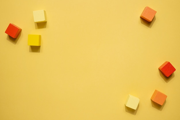 黄橙色の幾何学図形は静物画です。黄色の背景に木製のゲームキューブオブジェクト。シンプルコンセプトの上面図とシャドウ上面図