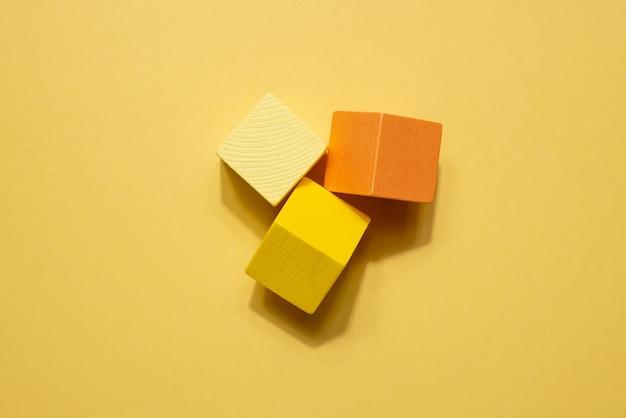 黄橙色の幾何学図形は静物画です。黄色の背景に木製のゲームキューブオブジェクト。シャドウトップとシンプルなコンセプトの上面図