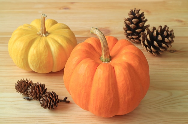 Yellow and orange pumpkins with natural dry pine cones on the wooden table