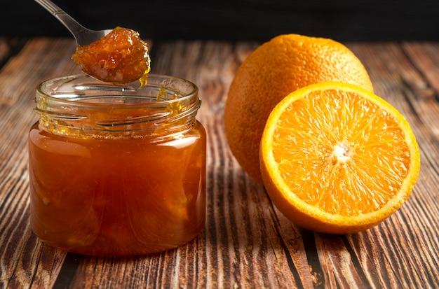 Желтые апельсины с банкой конфитюра.