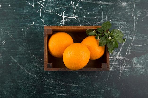 Желтые апельсины с зелеными листьями в деревянном ящике в центре