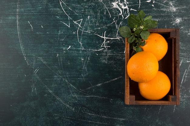 右側の木箱にある緑の葉と黄色いオレンジ