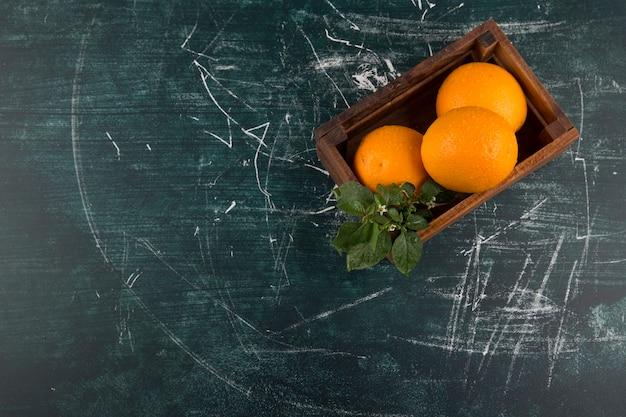 Желтые апельсины с зелеными листьями в деревянной коробке, вид сверху