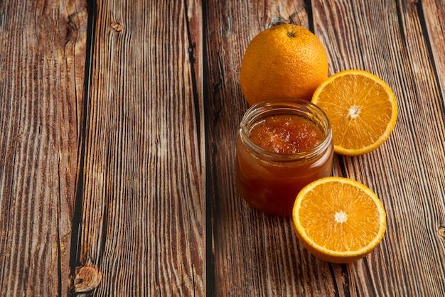 Arance gialle con un barattolo di confettura.