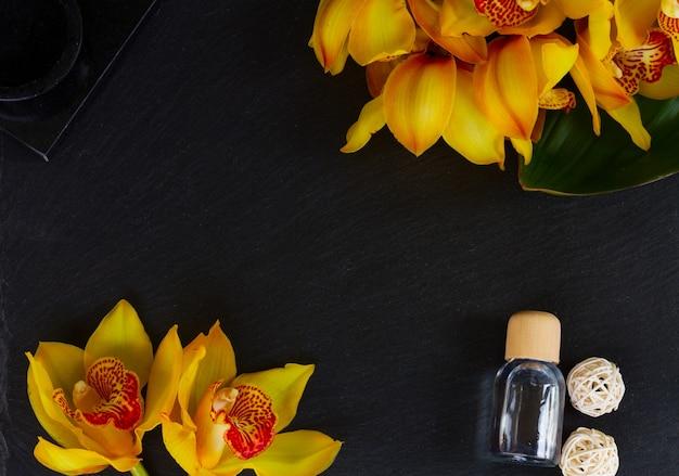 黒の背景に黄色の蘭の花スパフラットレイフレーム