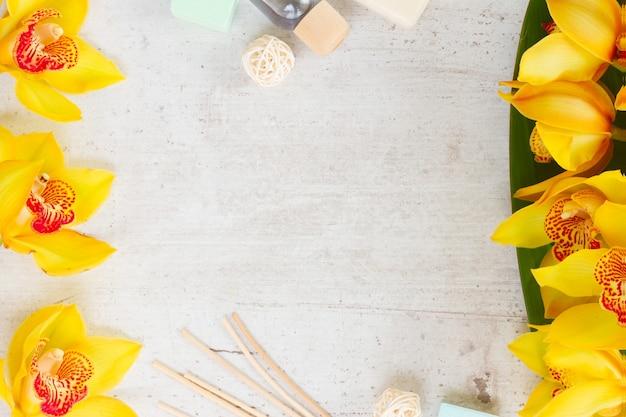 黄色い蘭の花スパフラットは、白い老化した背景にフレームを置きます