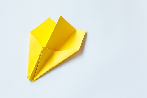 Yellow origami plane on a white wall.