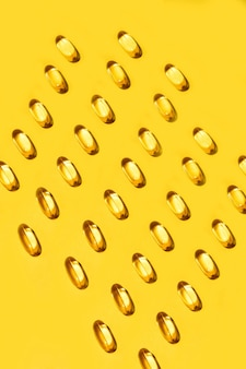 Yellow oval pills capsules vitamin omega 3 seamless pattern on yellow