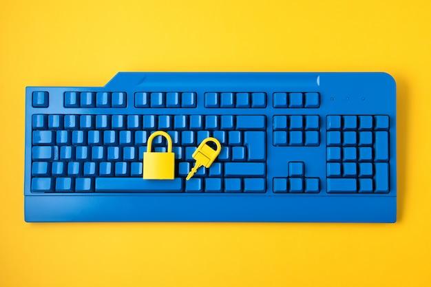 Yellow padlock and key and blue keyboard.