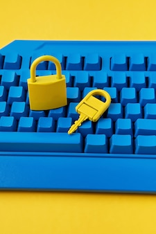 Yellow padlock and key and blue keyboard