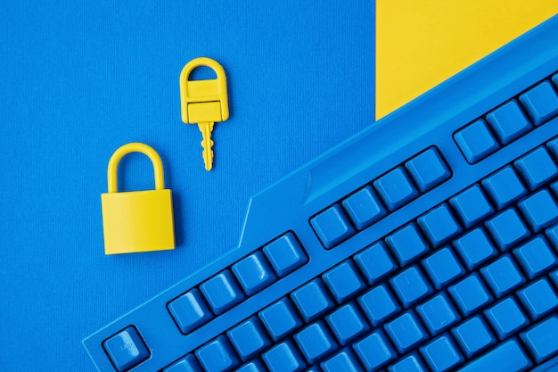 Yellow padlock and key and blue keyboard