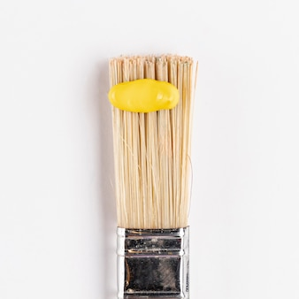 Yellow paint on brush with white background