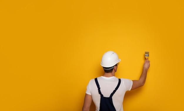 Желтая краска. крупным планом - мужчина в рабочем костюме и белом шлеме, красит стену желтым цветом.