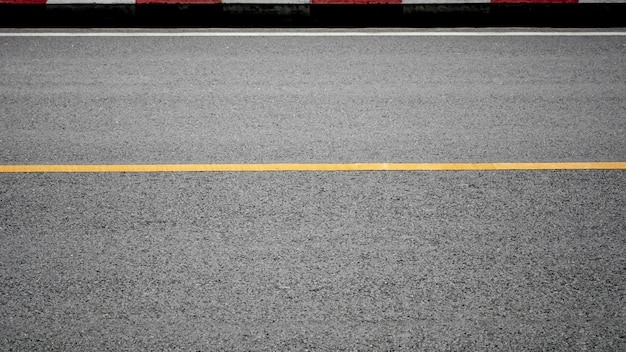 Yellow paint line on asphalt road - background
