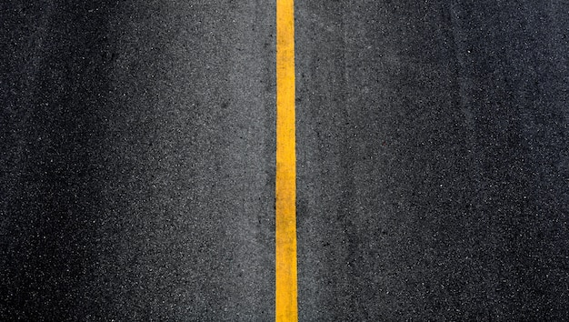 Yellow paint line on black asphalt