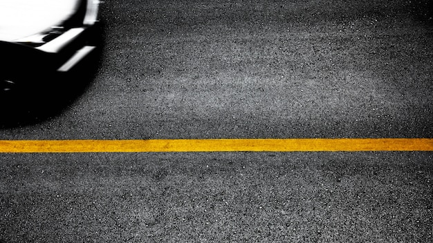 Yellow paint line on black asphalt