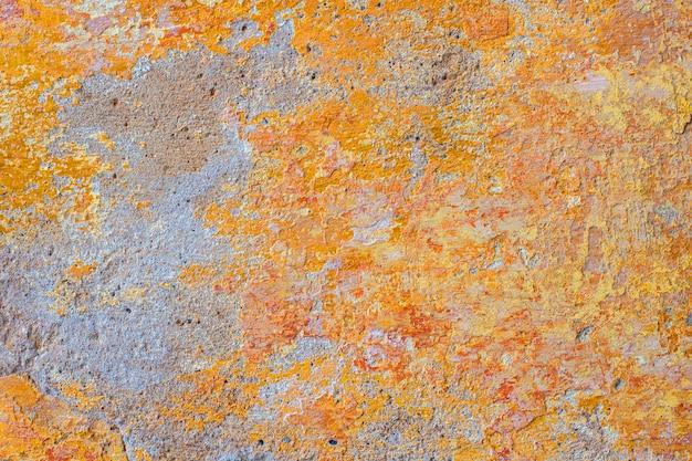 コンクリートの壁に黄色のペンキ。抽象的な背景。古い壁のテクスチャ。漆喰の粗面。