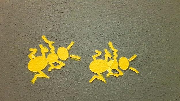 灰色の壁に黄色に塗られたアリ。壁を登るアリ。カラフルなアリの背景。地元の芸術家が通りの壁を飾ります。