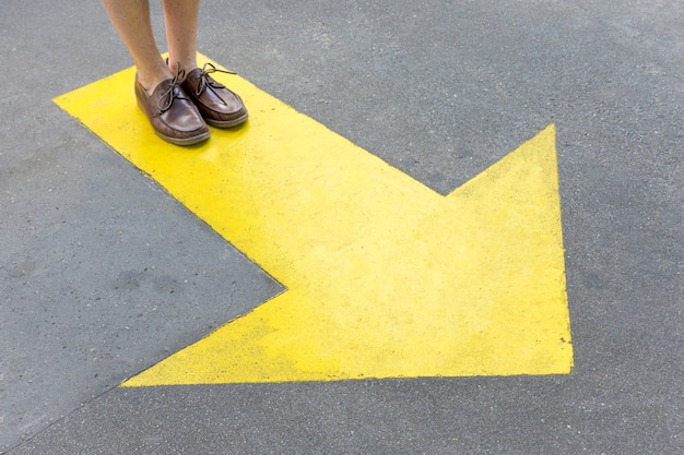 Yellow painted arrow in the streets and legs