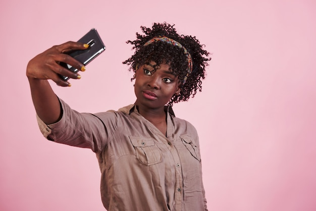Yellow painted fingernails. attractive afro american woman in casual clothes takes selfie at pink background in the studio
