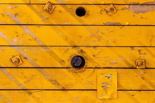 穴のある黄色に塗られた古い木の板。天然木の質感。抽象的な背景