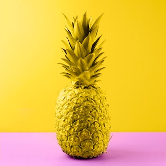 Yellow painted pineapple on pink desk against colored backdrop