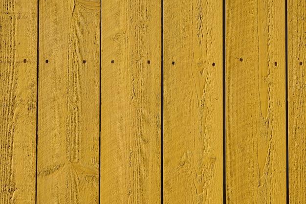 Желтая окрашенная редкая деревянная стена фоновой текстуры