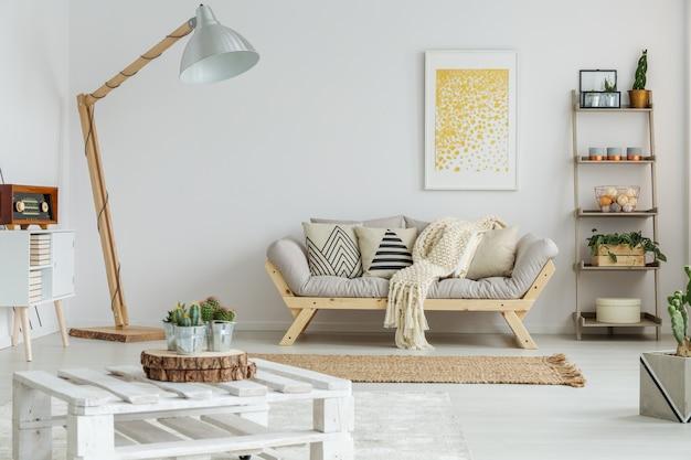 黄色の絵が装飾的なリビングルームの灰色のソファに掛かっています