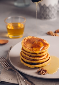 Yellow pancakes with corn flour and turmeric, dressed honey and red grapes