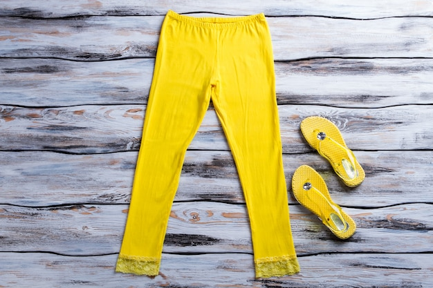 Yellow pants and flip flops. flip flops on wooden background. lady's bright summer footwear. elements of casual outfit.