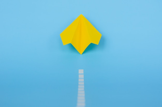 Yellow paper airplane moving up from runway on blue background. minimal travel and vacation concept.