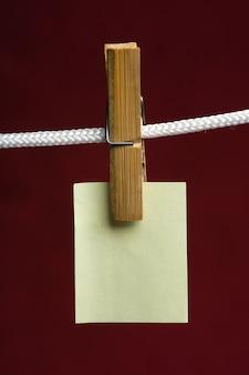 Желтая бумага прикрепляет прищепку к веревке на бордовом фоне