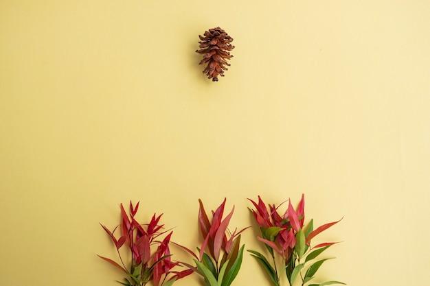 Желтая бумага фоновой текстуры с красными зелеными листьями и сосновыми цветами. минималистский стиль